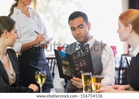 Handsome businessman ordering dinner from waitress in a restaurant - stock photo