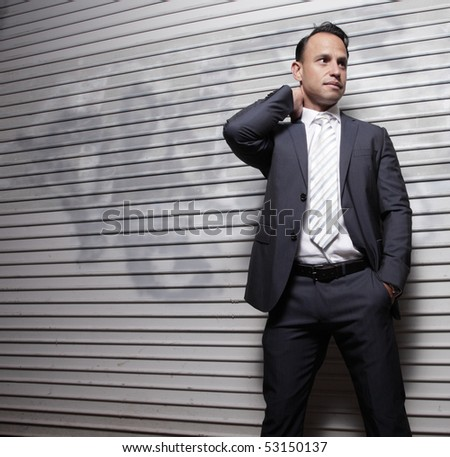 Handsome businessman posing by an urban abstract background