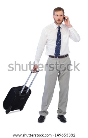 Handsome businessman posing with suitcase and phone against white background - stock photo
