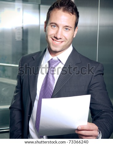Handsome businessman reading papers and smiling - stock photo