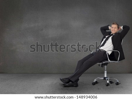 Handsome businessman resting in his swivel chair in a grey empty room - stock photo