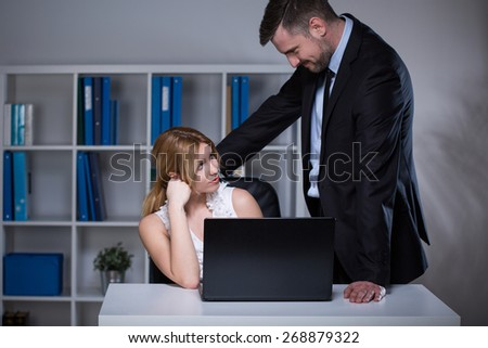 Handsome businessman seducing his beautiful younger assistant - stock photo