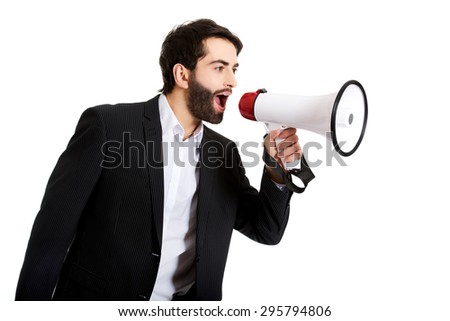 Handsome businessman shouting using a megaphone. - stock photo
