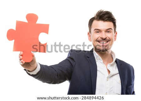 Handsome businessman showing a piece of jigsaw puzzle, over white background.