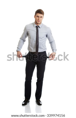 Handsome businessman showing his empty pockets. - stock photo