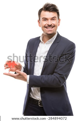Handsome businessman showing small jigsaw puzzle over white background.
