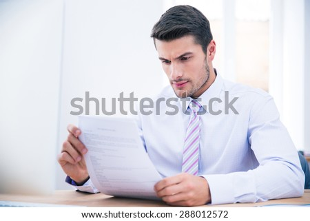 Handsome businessman sitting at the table reading document in office - stock photo