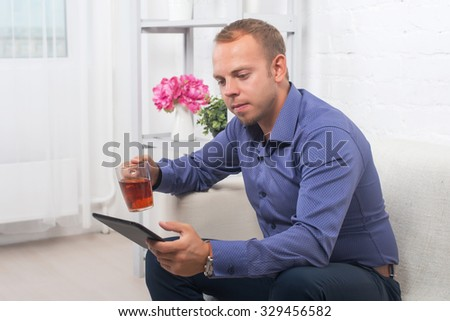 Handsome businessman sitting on couch with the tablet and working.