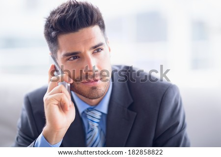 Handsome businessman sitting on sofa making a call in the office - stock photo