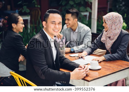 handsome businessman smiling at the camera during a business meeting - stock photo