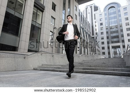 Handsome businessman standing on stairs of business center - stock photo