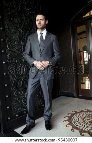 handsome businessman standing the door, fashion model - stock photo