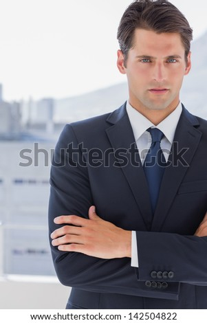 Handsome businessman standing with arms crossed in a bright office - stock photo