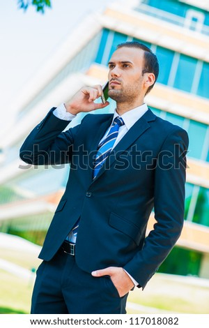 Handsome businessman talking over cellphone - stock photo