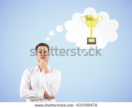 Handsome businessman thinking about golden cup trophy on blue background - stock photo