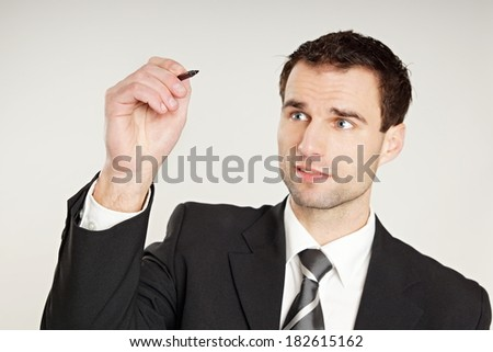 Handsome businessman thinks and writes with marker, focus is on the pen