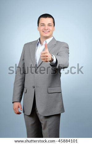 Handsome businessman thumb up on blue background - stock photo