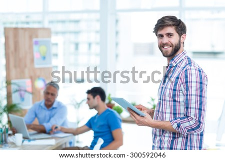 Handsome businessman using tablet in office - stock photo