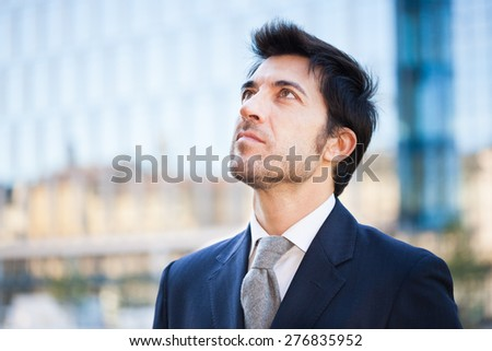 handsome businessman walking in an urban street - stock photo