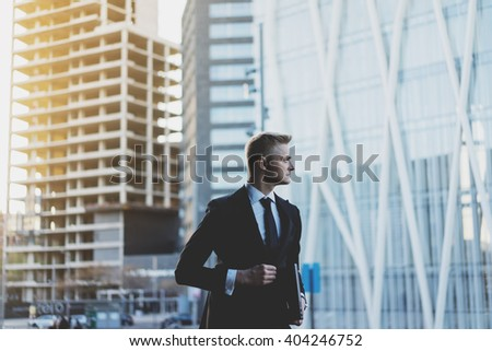 Handsome businessman wearing black suit and working on new project of modern office skyscrapers outside, flare light - stock photo