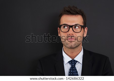 Handsome businessman wearing glasses looking up - stock photo