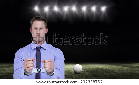 Handsome businessman wearing handcuffs against football pitch at night with ball and lights - stock photo