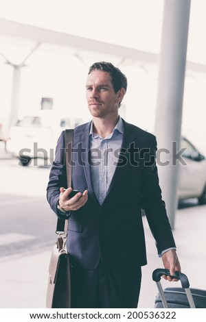 Handsome businessman with a suitcase leaving the airport - stock photo