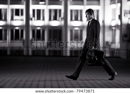 Handsome businessman with briefcase at night city in the background - wb image - stock photo