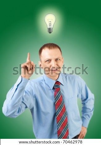 Handsome businessman with finger pointing up and with light bulb over his head, over green background - stock photo