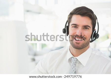 Handsome businessman with headset interacting in his office - stock photo