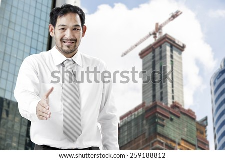 handsome businessman with open hand ready for handshake with the blur construction site background  - stock photo