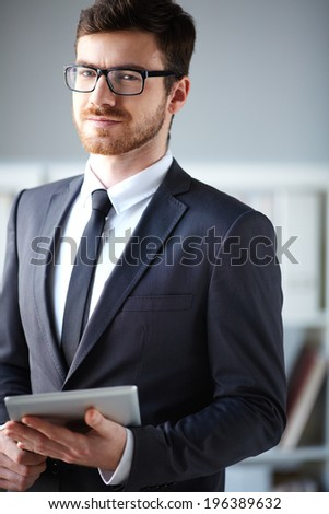 Handsome businessman with touchpad looking at camera - stock photo