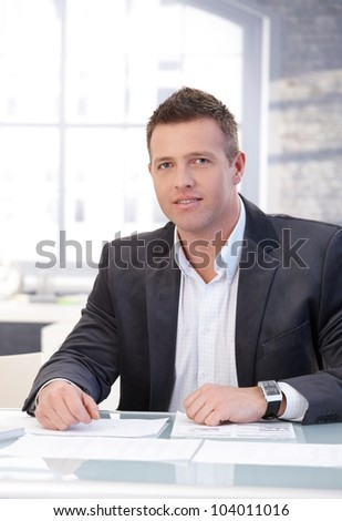 Handsome businessman working at desk in bright office. - stock photo