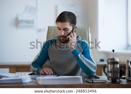 Handsome businessman working in office on the phone and doing paperwork he is very busy - stock photo