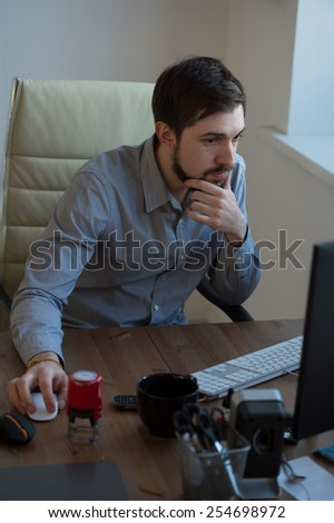 Handsome businessman working with computer in office - stock photo