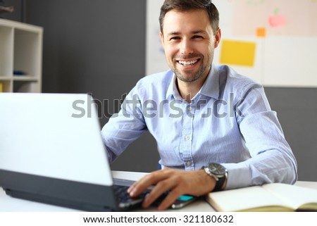 Handsome businessman working with laptop in office - stock photo