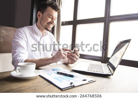 Handsome businessman writing massages with cup of coffee in restaurant. - stock photo