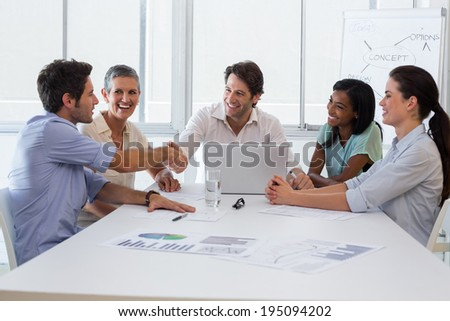 Handsome businessmen shaking each others hands after amazing presentation - stock photo