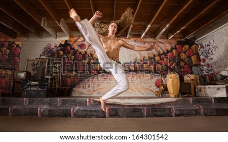 Handsome capoeira performers demonstrating a flying kick - stock photo