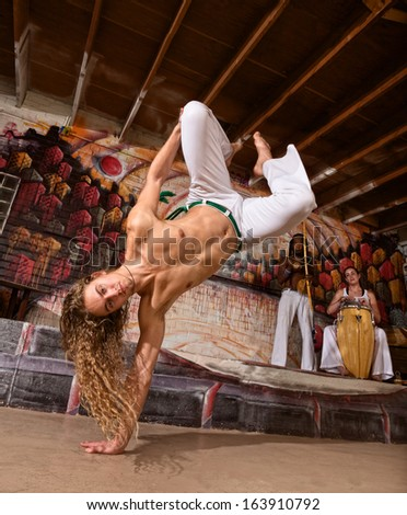Handsome capoeira performers leaping on to one hand - stock photo