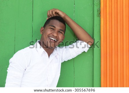 Handsome caribbean guy in front of a colorful wall - stock photo
