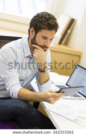 Handsome casual business man working on computer in modern office - stock photo
