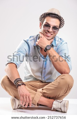 Handsome casual man smiling and sitting with his legs crossed while holding his left hand to his chin. - stock photo