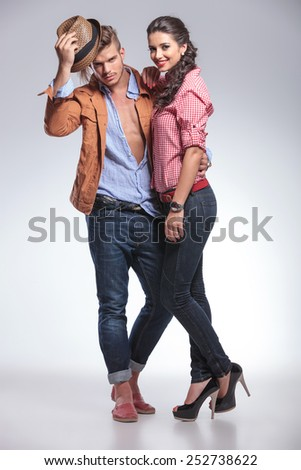 Handsome casual man taking off his hat while his girlfriend is smiling and leaning on him. - stock photo