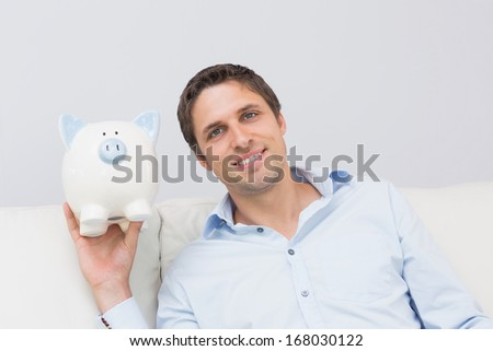 Handsome casual man with piggy bank in the living room at home - stock photo