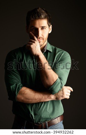Handsome casual young man looking at camera and slightly smiling. Men's beauty. Studio shot over black background. - stock photo