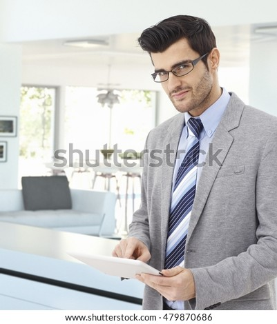 Handsome caucasian businessman at home with tablet in hand, wearing suit and glasses, standing, smiling, looking at camera. Pointing, bristly, business.