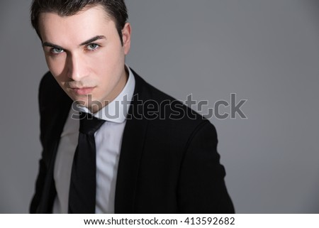 Handsome caucasian businessman looking at the camera on light grey background - stock photo