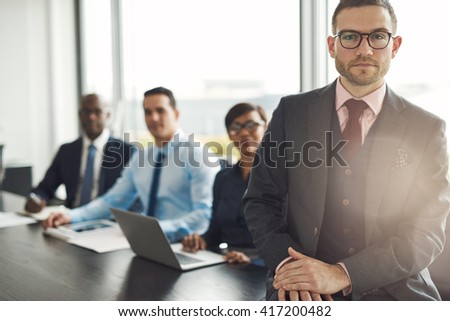 Handsome Caucasian executive with three employees sitting on edge table with back to large bright office window with light flare - stock photo