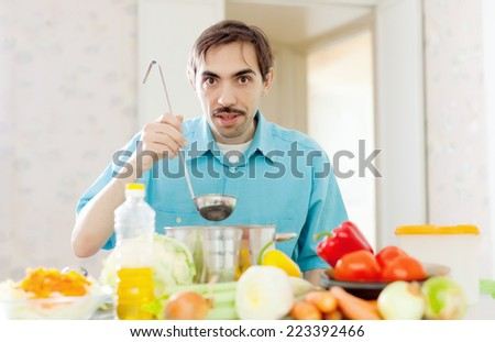 handsome caucasian guy cooking vegetables in pan at home - stock photo